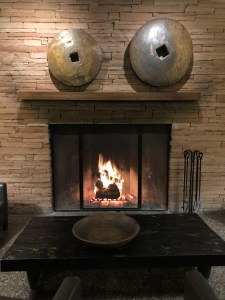 An image of a fire burning in a fireplace at the Enchantment Resort in Sedona Arizona, surrounded by brick work and an inviting setting