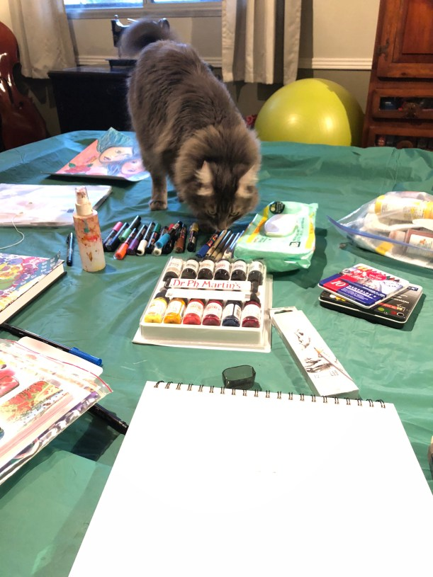 an image with the pool table covered in art supplies and the cat checking them out.