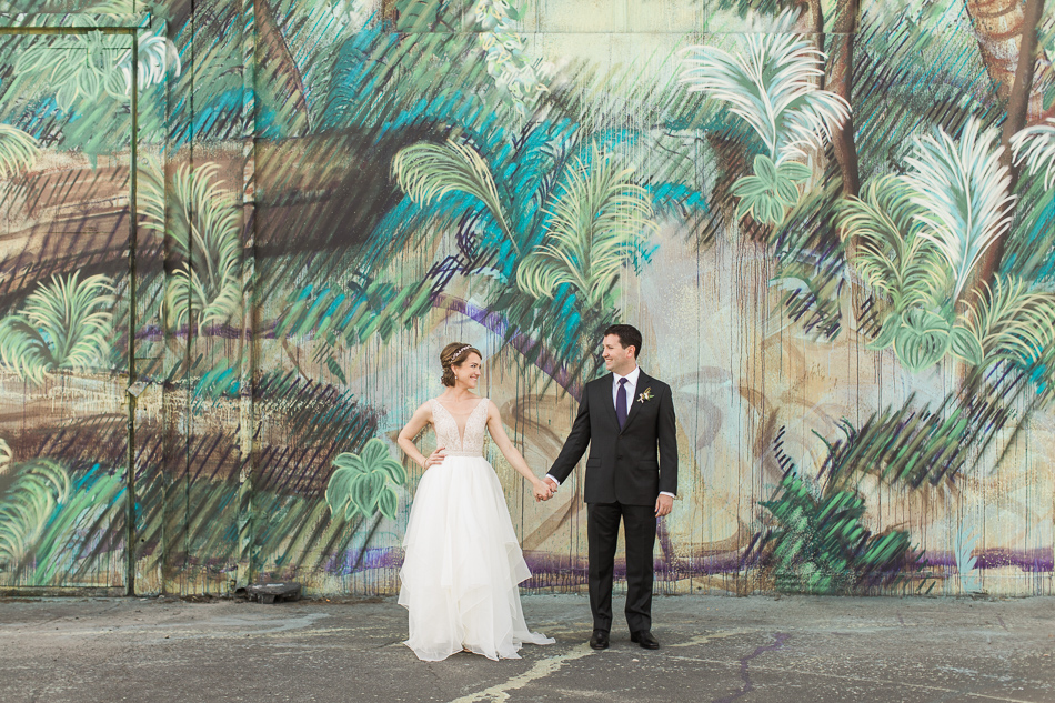 A bride and groom hold hands in front of a colorful mural during their elegant wedding at Canvas Event Space in SODO, Seattle, WA. | Joanna Monger Photography | Snohomish & Seattle Wedding Photographer
