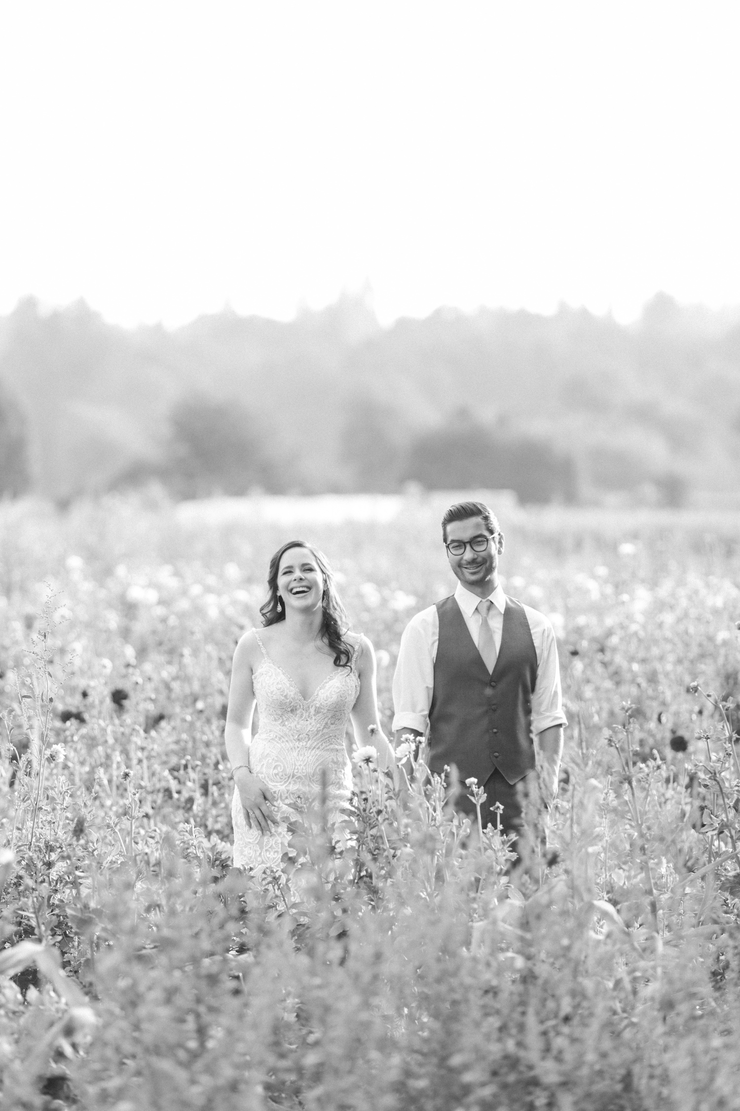 A black-and-white photo of a bride and groom laughing while standing in a field of flowers before their wedding atWoodland Meadow Farms in Snohomish, a wedding venue near Seattle, WA. | Joanna Monger Photography | Seattle & Snohomish Photographer