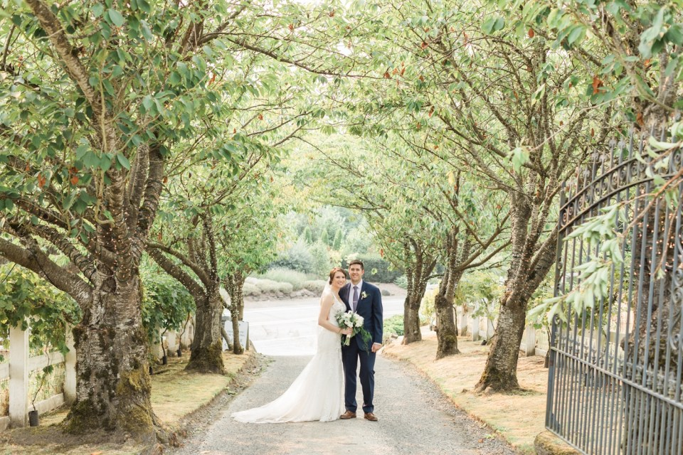 A bride and groom stand near the tree-lined entrance of Chateau Lill in Woodinville, a wedding venue near Seattle, WA. | Joanna Monger Photography | Seattle & Snohomish Photographer