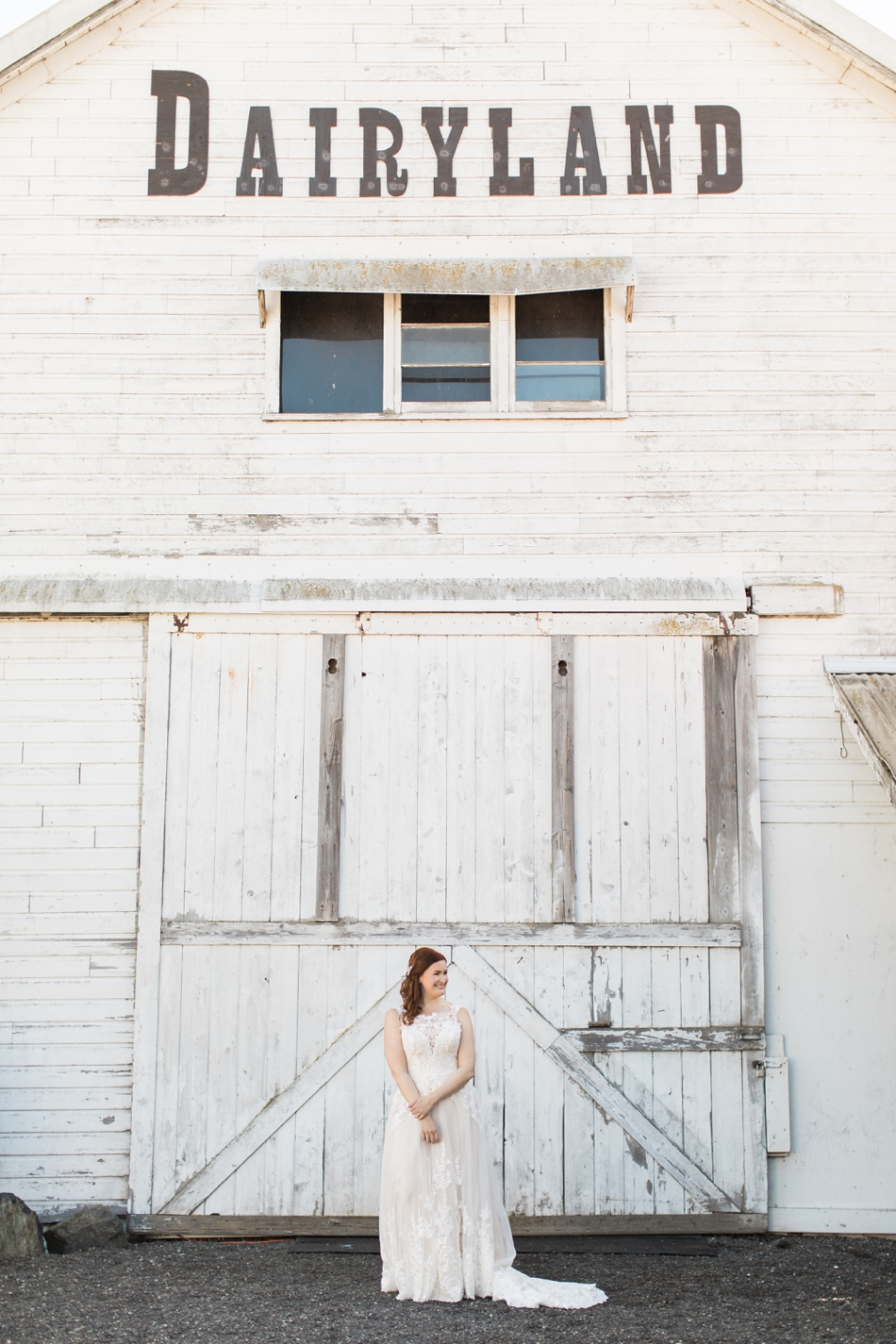 Photo of bride in front of white-wash barn at Snohomish Wedding Venue Dairyland Barn near Seattle | Joanna Monger Photography