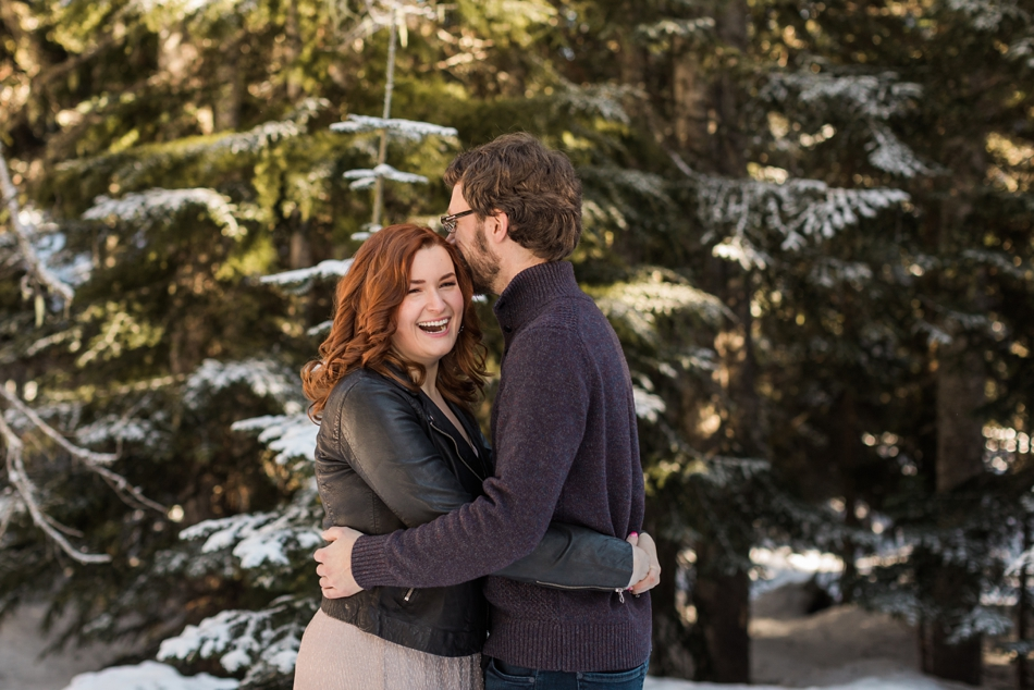 An engaged couple laughs while embracing in the snow during their Steven's Pass engagement shoot for their dreamy DIY wedding at Dairyland in Snohomish, a wedding venue near Seattle. | Joanna Monger Photography | Snohomish & Seattle Photographer