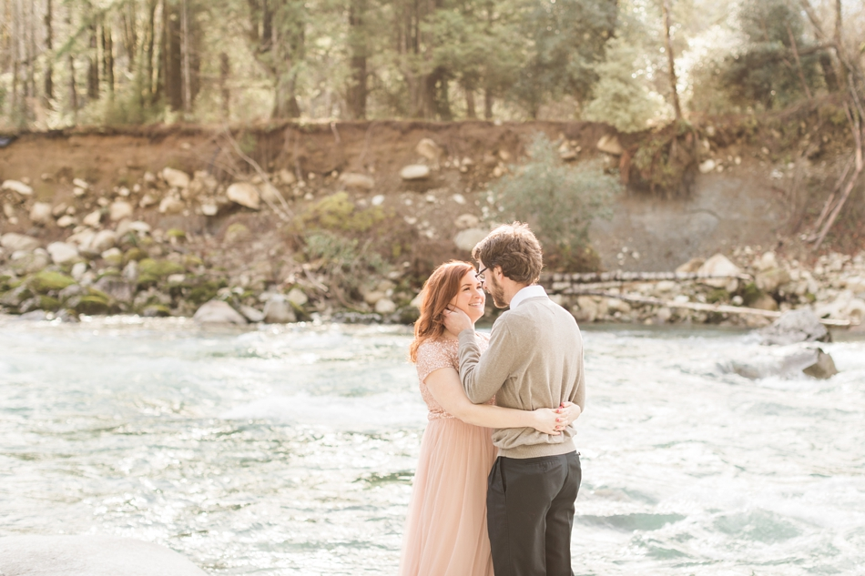 An engaged couple loving embraces near a river during their Steven's Pass engagement shoot for their dreamy DIY wedding at Dairyland in Snohomish, a wedding venue near Seattle. | Joanna Monger Photography | Snohomish & Seattle Photographer