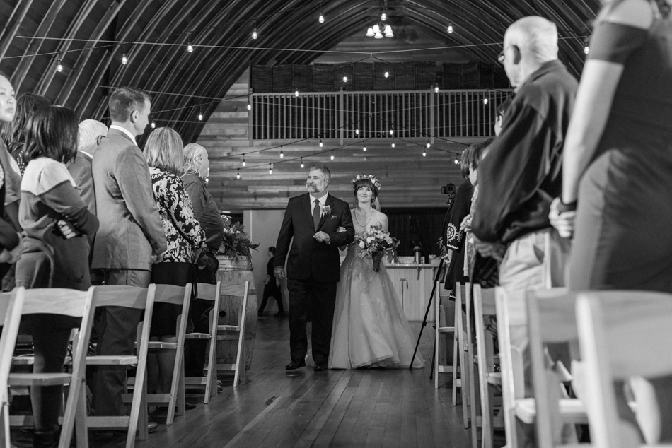 A black and white photo of a bride being accompanied down the aisle at her fall wedding at the Loft at Russell's in Bothell, a wedding venue near Seattle. | Joanna Monger Photography | Snohomish & Seattle Wedding Photographer