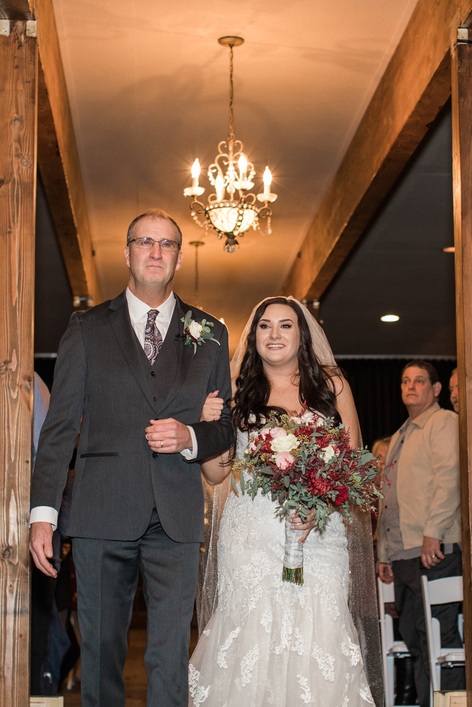 A photo of a groom walking his daughter down the aisle during the ceremony of her winter wedding at Hidden Meadows in Snohomish, a wedding venue near Seattle, WA. | Joanna Monger Photography | Snohomish & Seattle Wedding Photographer