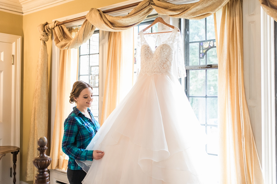 A bride looks at her wedding dress before getting ready for her regal winter wedding at Thornewood Castle in Lakewood, a wedding venue near Seattle, WA. | Joanna Monger Photography | Seattle & Snohomish Wedding Photographer