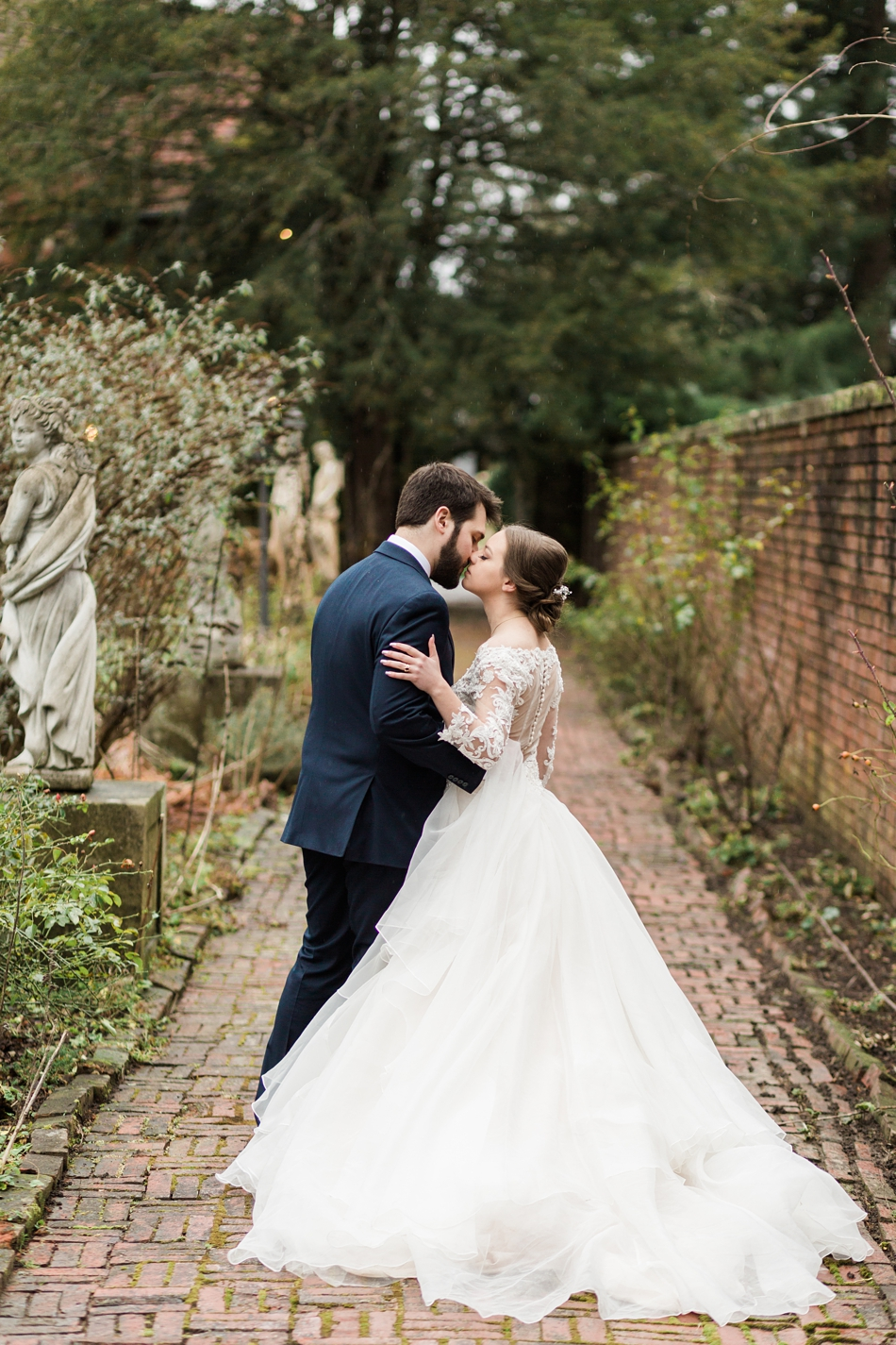 A bride and groom kiss on a brick path after their regal winter wedding at Thornewood Castle in Lakewood, a wedding venue near Seattle, WA. | Joanna Monger Photography | Seattle & Snohomish Wedding Photographer
