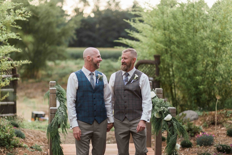 Grooms sharing a moment at Falling Water Gardens in Monroe. Photographs by Joanna Monger Photography, Award Winning Snohomish Wedding Photographer.