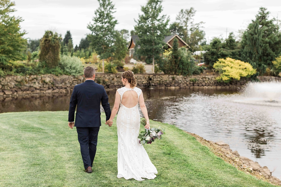Bride and groom walk hand in hand at Pine Creek Nursery in Monroe. Photographs by Joanna Monger Photography, Snohomish's Best Wedding Photographer.