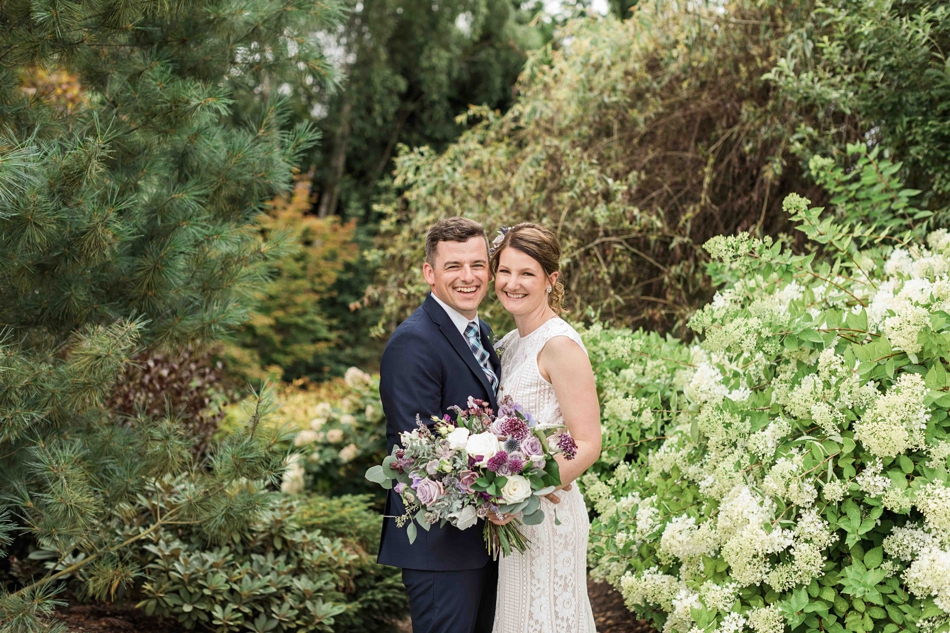 Bride and groom hold bouquet at Pine Creek Nursery in Monroe. Photos by Joanna Monger Photography, Snohomish and Seattle Wedding Photographer.
