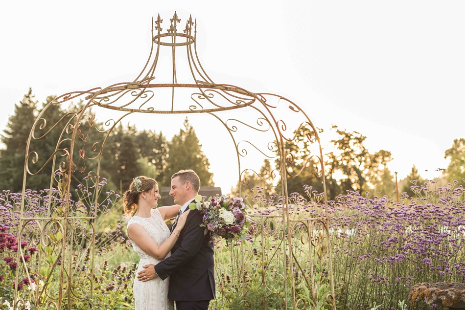 Holding each other under a trellis at Pine Creek Nursery in Monroe. Photos by Joanna Monger Photography, Snohomish and Seattle Wedding Photographer.
