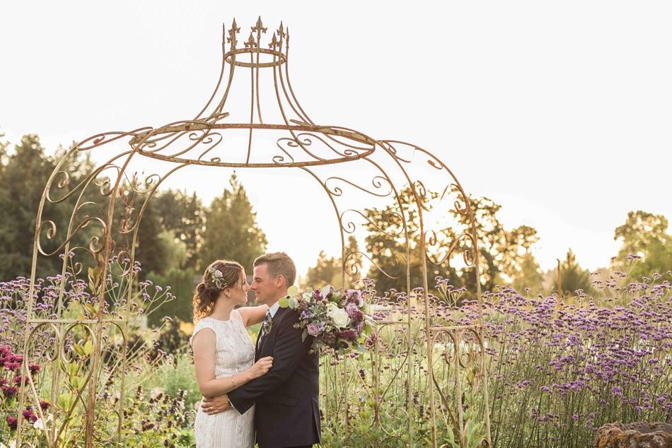Kissing under a trellis at Pine Creek Nursery in Monroe. Photographs by Joanna Monger Photography, Award Winning Snohomish Wedding Photographer.