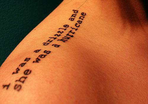 Typewriting quote tattoo design on upper shoulder
