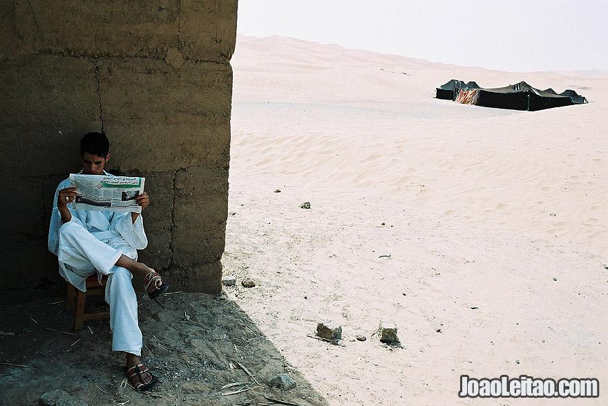 Photo of boy reading the newspaper in Sahara Desert, Morocco