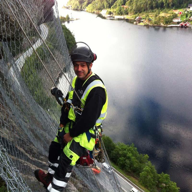Edin Mujkic hos Skoppum er ikke redd for høyder. Her er han fotografert under fjellsikringsarbeid i sommer. Foto: Skoppum Grunnarbeid