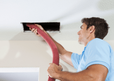 Technician vaccuuming out air ducts to reduce allergies
