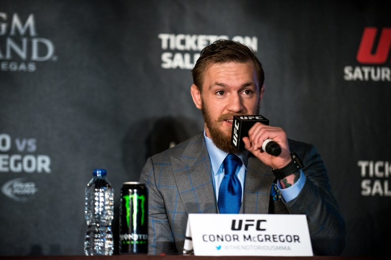 Conor McGregor speaks into a microphone during a press conference.