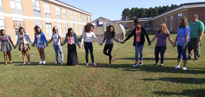 AVID students (from left) Koliah Street, Keja Stevens, Mckayla Ward, Rachel Harris, Samelia Wilder, Taya Bryant, December Watson, Neasha Williams, Sarah Reichard, and Lari Johnson are working together to get the hula hoop around the loop without breaking their hand hold in a record time. After several tries, this group of Smithfield-Selma High School AVID students were able to cut their time down from over three minutes to just under two minutes. The activity was designed to have students come up with a common strategy, work together, cheer each other on, set goals for themselves, and put in 100 percent effort. Standing off to the right is AVID Elective teacher Elliot Froehbrodt, who is observing how his students are working to accomplish the common goal.