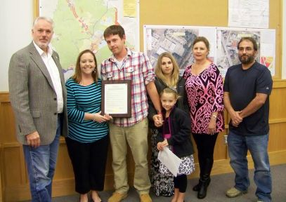 Smithfield Mayor John Lampe (left) presents a proclamation from the Smithfield Town Council to the family of slain Johnston County sheriff's deputy Clendon Paul West Sr. formally requesting the NC DOT rename the Market Street bridge in his memory. WTSB Photo