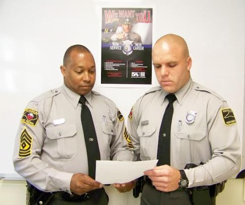 Johnston County Highway Patrol First Sgt. V.E. Burton (left) reads a thank you letter from a motorist assisted by Trooper Joshua Kiser (right) earlier this month on US 70 near Smithfield. JoCoReport.com Photo