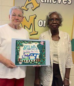 Selma Downtown Partnership Member Dina Flowers (left) and Selma Mayor ProTem Jackie Lacey (right) show Tajiya Davis' winning poster design.