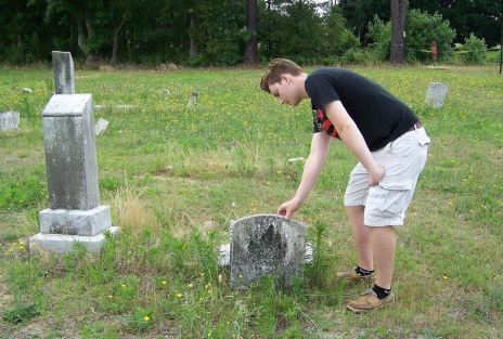 Boy Scout Isaac Wells examines a headstone knocked from its base at an abandoned cemetery on US 301 in Selma.  Wells will spend this summer restoring the 140 graves in the cemetery, which was heavily vandalized 10 to 20 years ago and has no regular upkeep. JoCoReport.com Photo