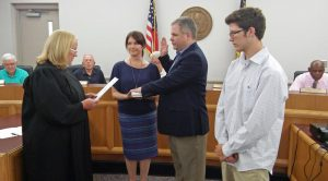 Four Oaks Town Councilman Andrew Hardy receives his Oath of Office from District Court Judge Joy Jones (far left) as his wife, Donnie, holds the Bible. Their son Ryan (far right) looks on.  JoCoReport.com Photo