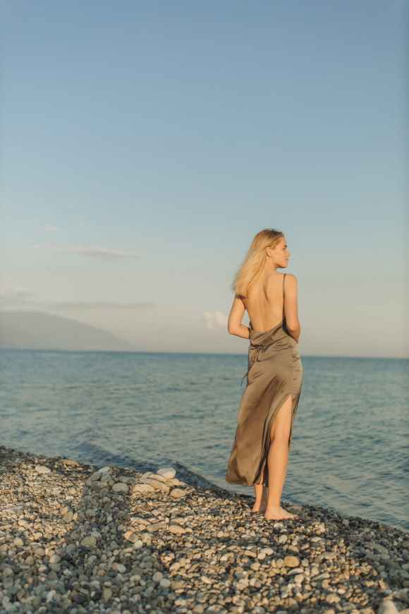 woman in brown spaghetti strap dress standing on rocky shore