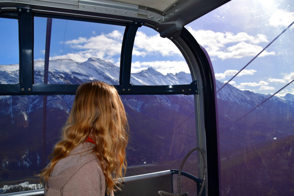 girl looking at mountains from gondola