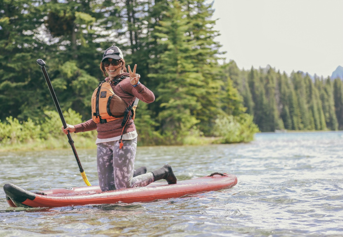 woman paddle boarding in the mountains
