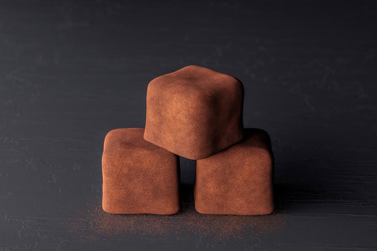 Dusted chocolate truffle squares on slate CGI