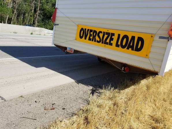 License plate and oversize load banner on trailer hauling the tiny house.