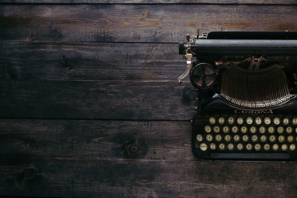 black corona typewriter on brown wooden planks