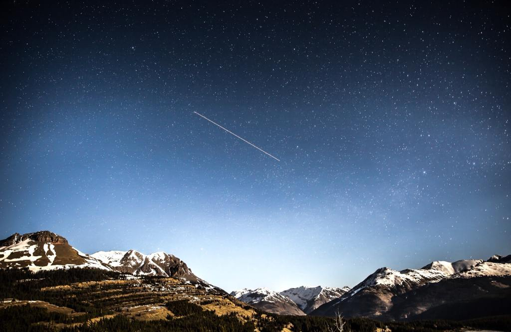 shooting star over snow covered mountains