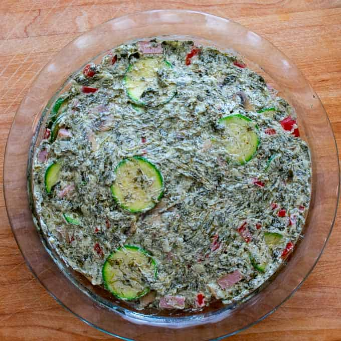 Overhead view of pie plate with quiche ingredients ready to put into the oven.