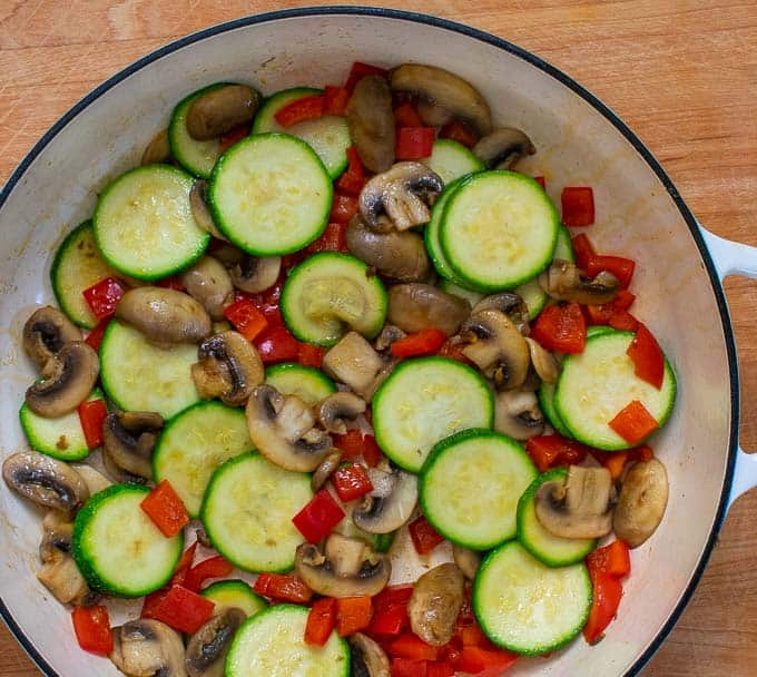 Dutch oven with sauteed mushrooms, red bell pepper, and zucchini.