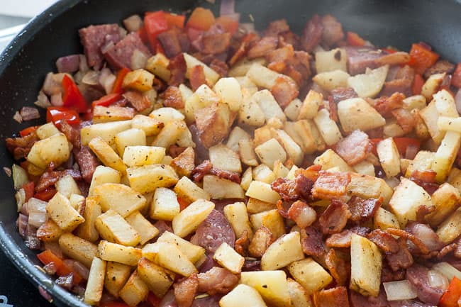 Adding the bacon and potatoes back into the skillet.