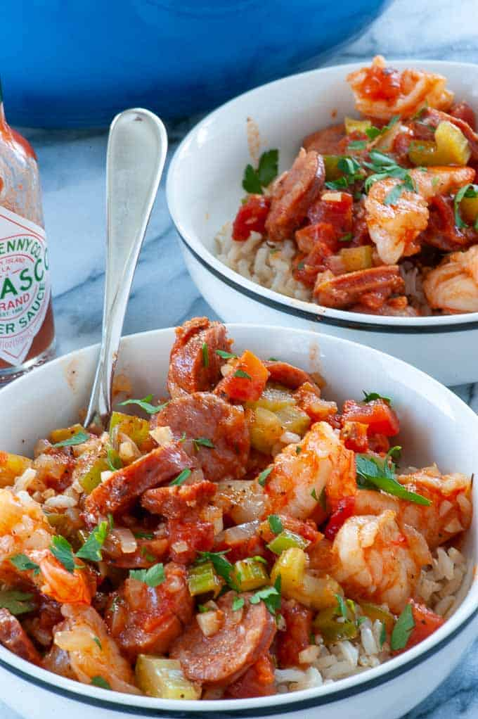 Two bowls of sausage and shrimp jambalaya over rice, ready to eat.