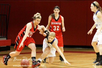 Blakelee Cooper (#23) of the Hoisington Lady Cardinals drives through Russell Lady Broncos defender Madison Beagley (#12) at the 2012 Hoisington Winter Jam Basketball Tournament.