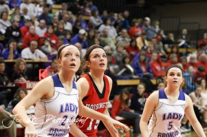 Russell Lady Broncos Kelli Rourke (#21) and Alex Ptacek (#5) watch a free throw attempt along with Savannah Rose (#15) of the Hoisington Lady Cardinal at the 2012 Hoisington Winter Jam Basketball Tournament.