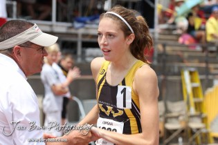 An official congratulates Shawnee Mission West's Alli Cash on her Class 6A 1600 Meter Run record of 4:52 during the 2012 KSHSAA State Track and Field Championship at Cessna Stadium on the campus of Wichita State University in Wichita, Kansas on May 26, 2012. (Photo: Joey Bahr, www.joeybahr.com)