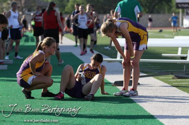 Two Trego Community High School runners comfort a fellow member of the 4x800 Meter Relay team during the 2013 KSHSAA Class 1A Regional Track and Field competition at Lewis Field on the campus of Fort Hays State University in Hays, Kansas on May 17, 2013. (Photo: Joey Bahr, www.joeybahr.com)
