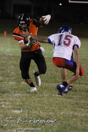 Larned Indian Isiah Perez (#84) evades the tackle of Ellinwood Eagle Tate Fisher (#15) during the Ellinwood versus Larned High School football game with the Larned Indians winning 60 to 0 at Larned High School in Larned, Kansas on September 13, 2013. (Photo: Joey Bahr, www.joeybahr.com)