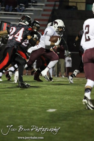 Salina Central Mustang Malik Veal (#1) drives through the Great Bend Panther line during the Salina Central versus Great Bend High School Football game with Salina Central winning 41 to 14 at Memorial Field in Great Bend, Kansas on October 25, 2013. (Photo: Joey Bahr, www.joeybahr.com)
