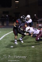 Salina Central Mustang Zane Heigele (#27) tackles Great Bend Panther Jonathan Allende (#21 ) for a loss during the Salina Central versus Great Bend High School Football game with Salina Central winning 41 to 14 at Memorial Field in Great Bend, Kansas on October 25, 2013. (Photo: Joey Bahr, www.joeybahr.com)