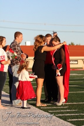 The Past Queen puts on the robe to the newly crowned Queen, Deiah Curtis, during the 2013 Hoisington High School Homecoming Festivities prior to the Larned at Hoisington Football game at Elton Brown Field in Hoisington, Kansas on October 11, 2013. (Photo: Joey Bahr, www.joeybahr.com)