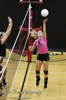 Hoisington Lady Cardinal Abi Rziha (#21) tips the ball over the net during the Hoisington versus Smoky Valley volleyball match with Hoisington winning in two sets at Hoisington Activity Center in Hoisington, Kansas on October 22, 2013. (Photo: Joey Bahr, www.joeybahr.com)