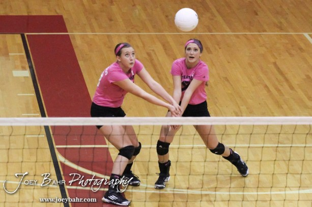 Hoisington Lady Cardinal Ashley Lockwood (#13) and Abbi Demel (#8) both go to dig a ball during the Hoisington versus Smoky Valley volleyball match with Hoisington winning in two sets at Hoisington Activity Center in Hoisington, Kansas on October 22, 2013. (Photo: Joey Bahr, www.joeybahr.com)
