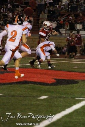 Hoisington Cardinal Avery Urban (#23) carries the ball as he is pursued by three Larned Indians during the Larned at Hoisington High School Football game with Hoisington winning 27 to 9 at Elton Brown Field in Hoisington, Kansas on October 11, 2013. (Photo: Joey Bahr, www.joeybahr.com)